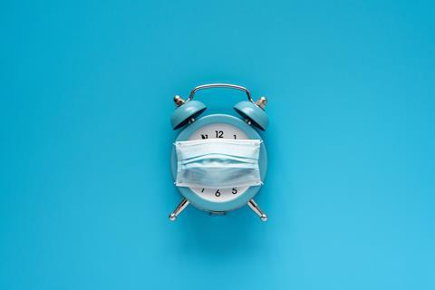 An image showing an alarm clock with a face mask on