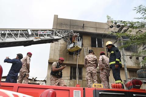 آتش نشانان و پرسنل جستجو و نجات در پشت یک ماشین آتش نشانی