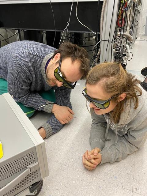 A photo showing two young scientists wearing yellow-tinted goggles, lying on the floor of an instrument room staring at a screen in front of them