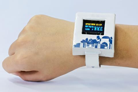 An image showing a person's wrist with a large white box strapped to it