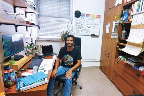 A photograph showing Jose Flroes-Livas in his office