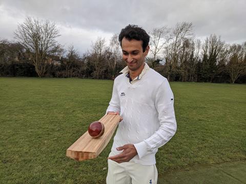An image showing a man holding a bamboo cricket bat