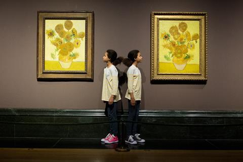 A photo of two versions of van Gogh's Sunflowers paintings hanging next to each other in a museum. Between them, standing back to back, are two Black girls, twins, wearing identical striped shirts but different coloured shoes (one pink, one grey).