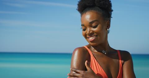 A smiling woman applies sunscreen