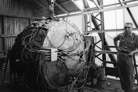 A black and white photo showing Norris Bradbury next to the Trinity test atomic bomb.  The device consists of a metal housing that is slightly higher than Bradbury and has cables in various places.