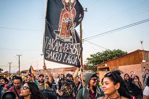 عکسی که نشان می دهد گروه بزرگی از مردم زیر آسمان آبی پرچمی در دست دارند که روی آن نوشته شده است