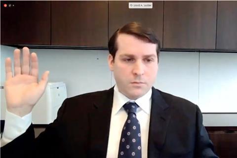 مردی در تماس تصویری دست خود را بلند می کند تا قسم بخورد