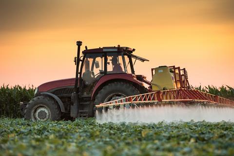Tractor rociando pesticidas en campo vegetal