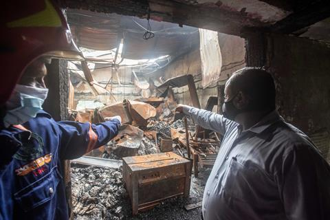 One picture shows two men pointing to the consequences of a chemical fire